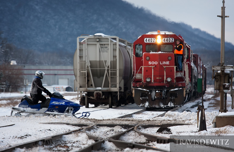 "The Canadian Pacific local job does some work in Lake City, Minnesota as a few snowmobilers cross the track on the nice winter day.  Travis Dewitz <a href=""http://www.therailroadcollection.com/latest-works/"" target=""_blank"">The Railroad Collection</a>"