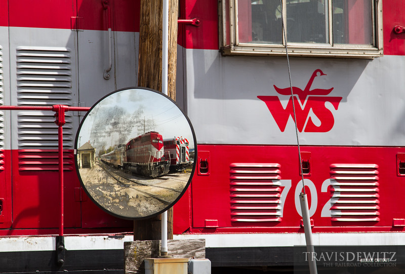 A Wisconsin and Southern GP7 crosses the grade crossing as the blind spot mirror reveals another unit and from what I hear, the WSOR passenger car fleet that is no longer in the state of Wisconsin.