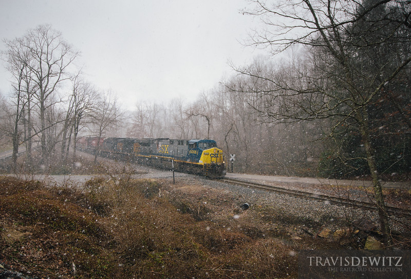 A winter snow squall releases heavy snow while a RJ Corman piloted empty coal train works towards Pax, West Virginia to load with coal.