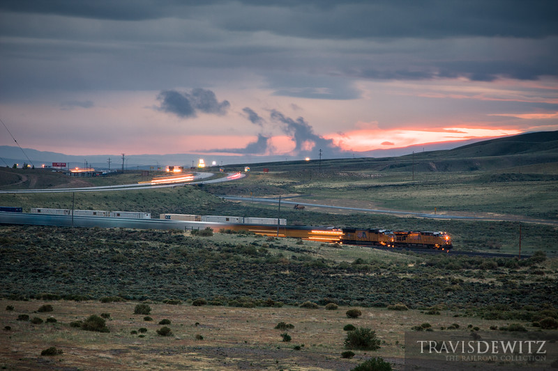 A Union Pacific stack train stops to let a grain train by before dawn outside Rawlins, Wyoming.
