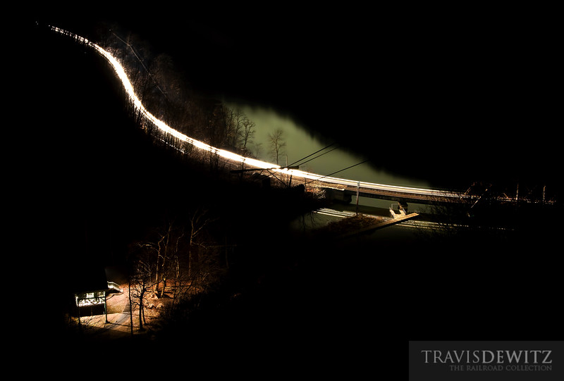 """The only lights on this moonless night are from a little cabin in the woods and a CSX coal train snaking along the New River inside the New River Gorge.  Travis Dewitz <a href=""""http://www.therailroadcollection.com/latest-works/"""" target=""""_blank"""">The Railroad Collection</a>"""