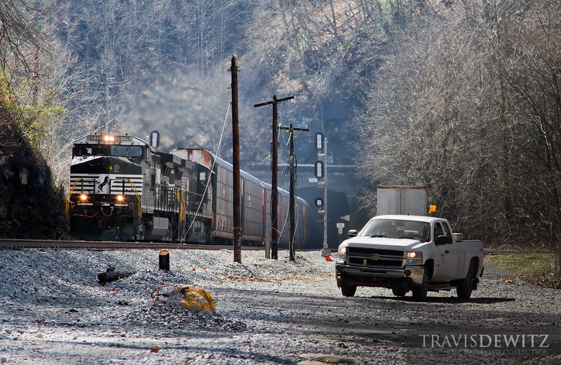 """a Norfolk Southern hi railer truck sits between Roderfield Tunnels as an autorack rushes by led by NS 9776.  Travis Dewitz <a href=""""http://www.therailroadcollection.com/latest-works/"""" target=""""_blank"""">The Railroad Collection</a>"""