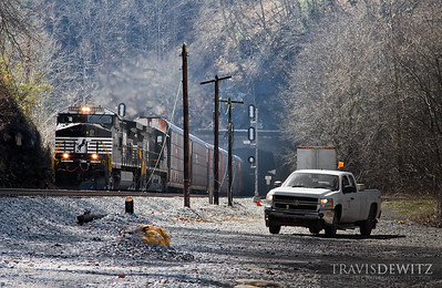 a Norfolk Southern hi railer truck sits between Roderfield Tunnels as an autorack rushes by led by NS 9776.  Travis Dewitz The Railroad Collection