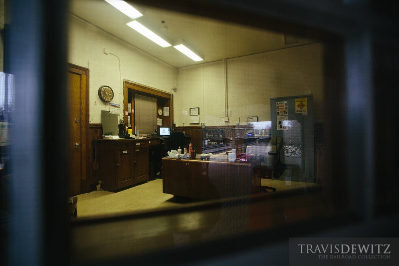 Looking into the Metra station office at Lake Bluff, Illinois. Every station office must always have a clock within view but not all have a red phone. The tracks are reflected in the window from behind me.