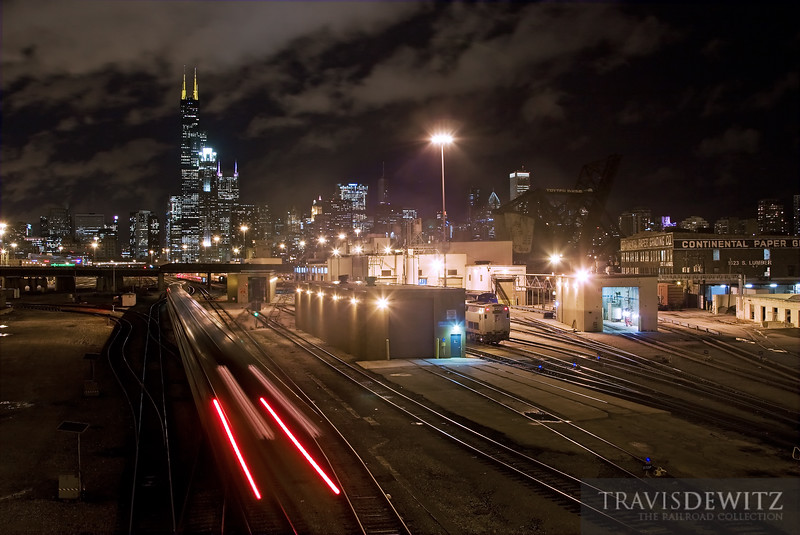 "An Amtrak passenger train streaks towards the Chicago skyline and Union Station.  Travis Dewitz <a href=""http://www.therailroadcollection.com/latest-works/"" target=""_blank"">The Railroad Collection</a>"