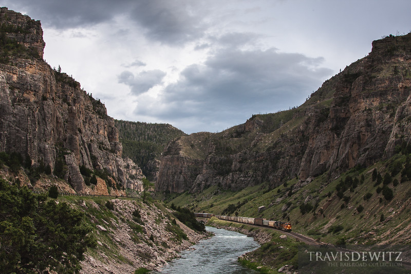 A BNSF freight train snakes along theriver and through Wind River Canyon nearing Thermopolis, Wyoming.