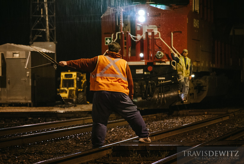 Rondout Tower operator hands off orders via hoop in the rain to a Canadian Pacific freight heading south into Chicago.