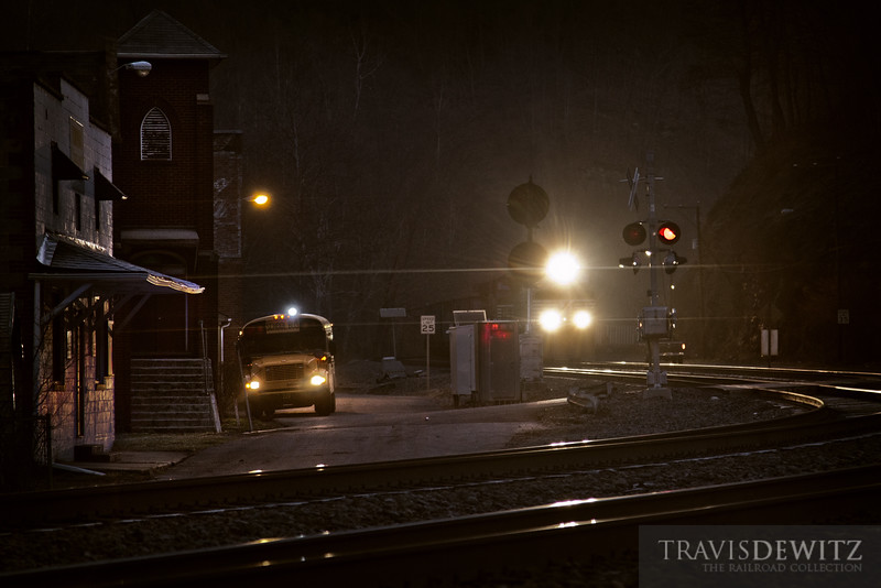 """Children get pick up for school in the early dawn hours in Keystone, West Virginia while a Norfolk Southern coal train glides downgrade through the dark town.  Travis Dewitz <a href=""""http://www.therailroadcollection.com/latest-works/"""" target=""""_blank"""">The Railroad Collection</a>"""