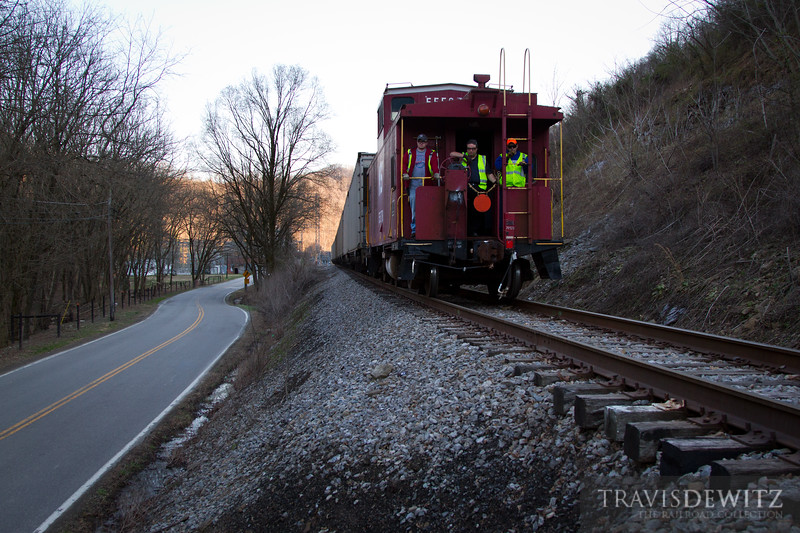 A  Norfolk Southern coal train backs up to the Lobata loadout with a NW caboose and crew on the rear protecting the shove move.