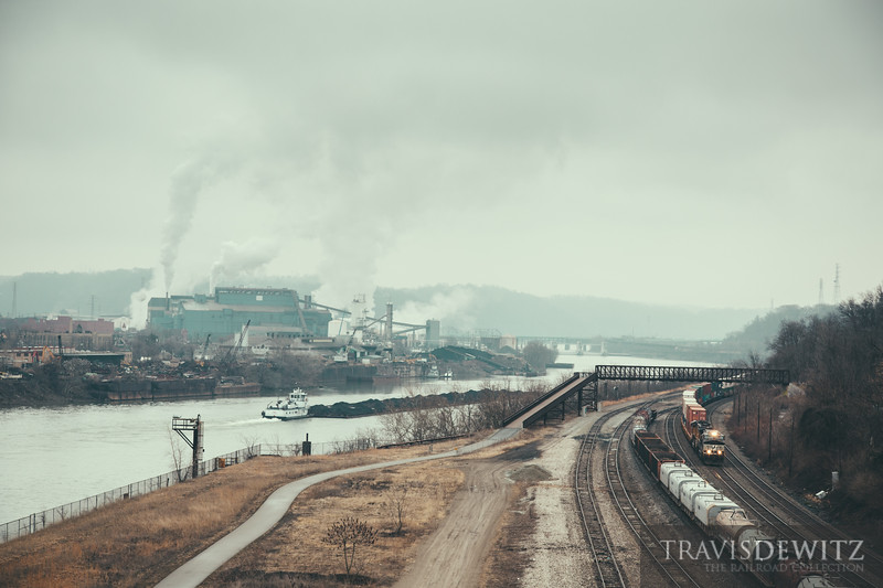 Steam fills the air of the US Steel Mon Valley Works Edgar Thompson steel plant that sits along the Monongahela River in Braddock, Pennsylvania. A barge of coal against the current up the river as a Norfolk Southern train works north.