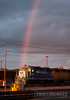 A bright rainbow shines down across the front of GMTX 2671 GP 38-2 in Altoona, Wisconsin.