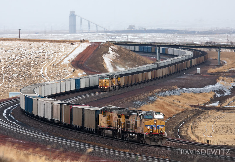 """Coal Creek Mine's loadout can be seen towering over the Powder River Basin as two Union Pacific train pass each other through the S curve just a few miles northeast of Wright, Wyoming.  Travis Dewitz <a href=""""http://www.therailroadcollection.com/latest-works/"""" target=""""_blank"""">The Railroad Collection</a>"""