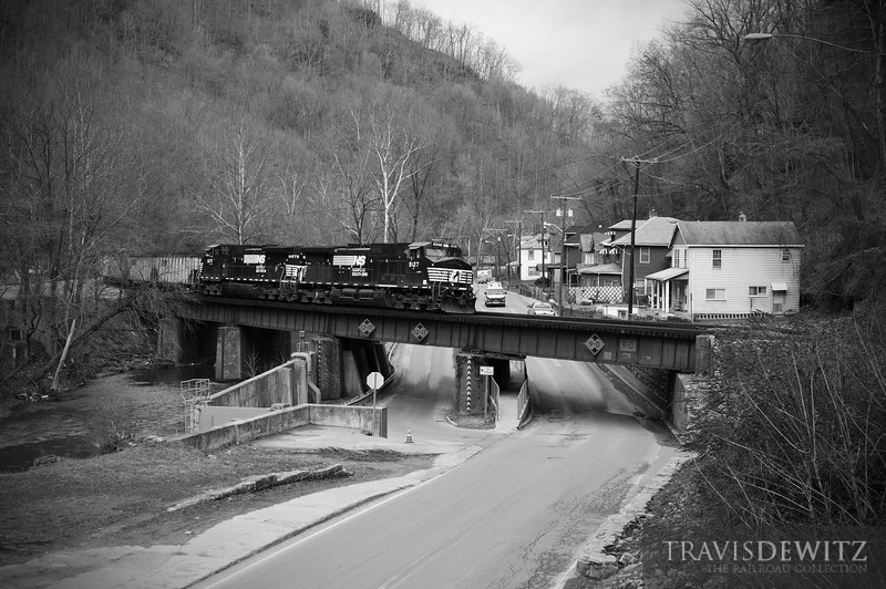 "Loaded hoppers full of coal are behing Norfolk Southern power as they curve through the city of Welch, West Virginia heading east towards Bluefield.  Travis Dewitz <a href=""http://www.therailroadcollection.com/latest-works/"" target=""_blank"">The Railroad Collection</a>"