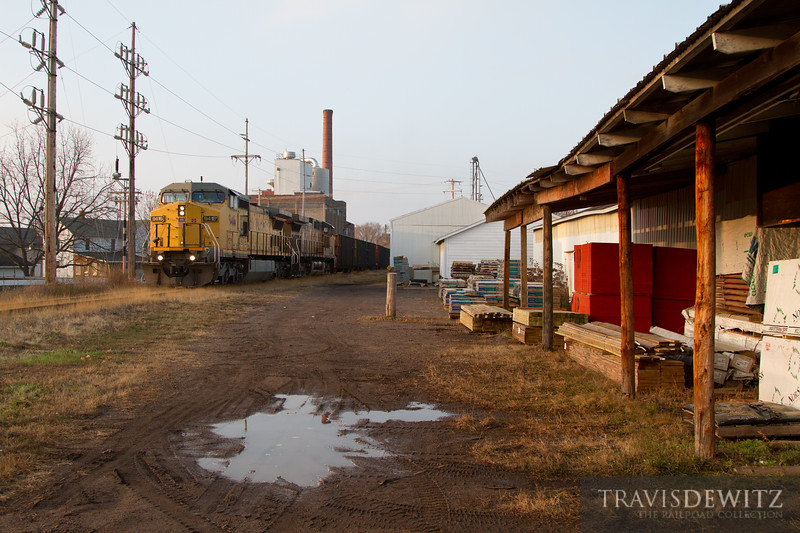 A frac sand train rolls south on the Wiscon Northern through Bloomer, Wisconsin past a lumber company.