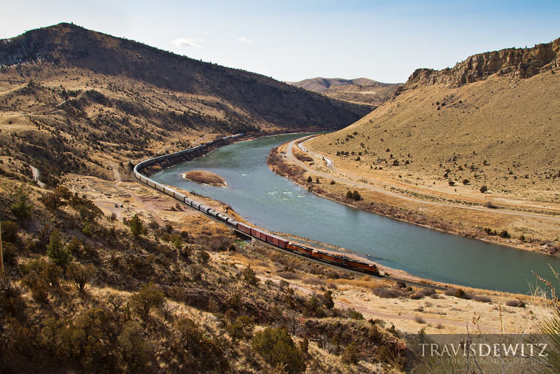 A BNSF trackage rights train snakes along the Missouri River as it makes its way out of Lombard Canyon as they approach Toston, Montana.