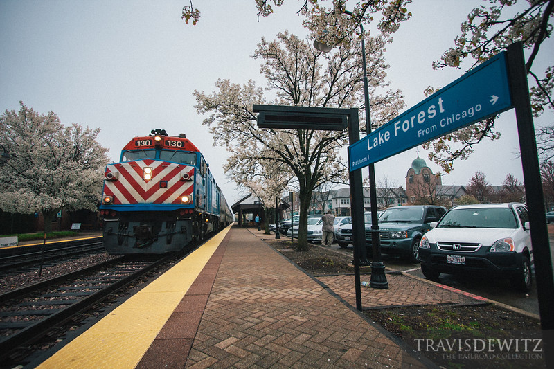 A Metra train slowly comes to a stop at the Lake Forest station on a dreary day.