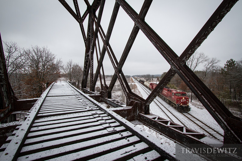 Canadian Pacific 8822 charges through the fresh snow and under the old C&NW steel truss bridge near the Fort McCoy Military area.