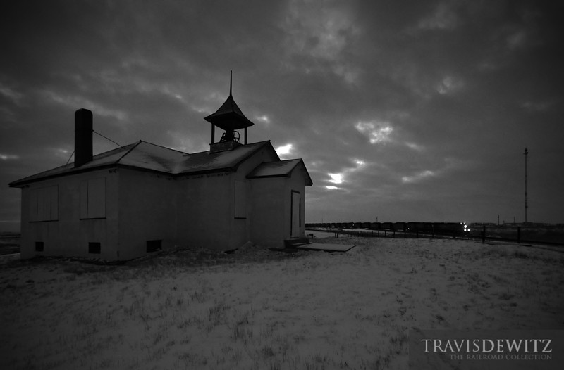 """Coal moves out the Powder River Basin past an abandoned school house in Shawnee, Wyoming as darkness covers the landscape.  Travis Dewitz <a href=""""http://www.therailroadcollection.com/latest-works/"""" target=""""_blank"""">The Railroad Collection</a>"""
