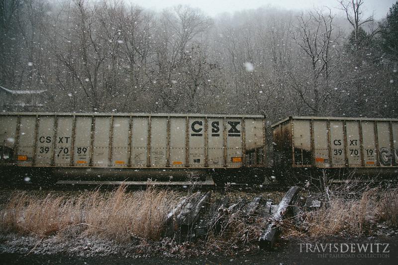 A parade of CSX coal hoppers pass through the snow in Thurmond, West Virginia.