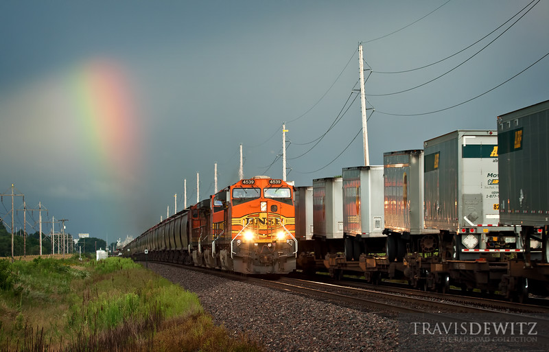 """A BNSF grain train passes a Z train as it heads west just outside Cochrane, Wisconsin as a passing thunderstorm leaves a rainbow in its path.  Travis Dewitz <a href=""""http://www.therailroadcollection.com/latest-works/"""" target=""""_blank"""">The Railroad Collection</a>"""