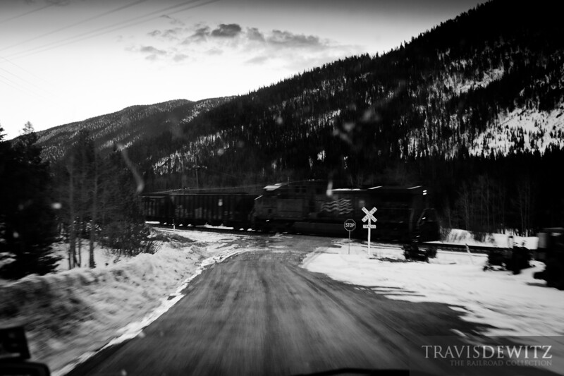 A loaded coal train heads down the mountain towards Denver on the Moffat Route as the DPU flies across the dirt mountain road crossing near Portal, Colorado.