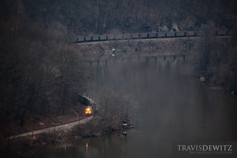 Early morning CSX train works along the New River as it glides by an old building on the rivers edge.