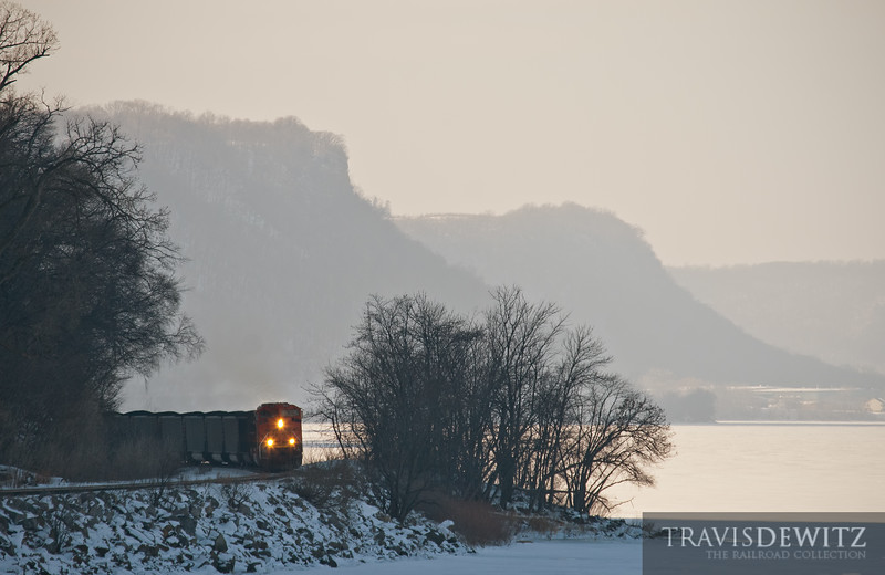"""Powder River Coal heads down the Canadian Pacific's River Subdivision along the Mississippi River being pulled by a BNSF SD70ACE. Lake City can be seen across the ice in the background.  Travis Dewitz <a href=""""http://www.therailroadcollection.com/latest-works/"""" target=""""_blank"""">The Railroad Collection</a>"""