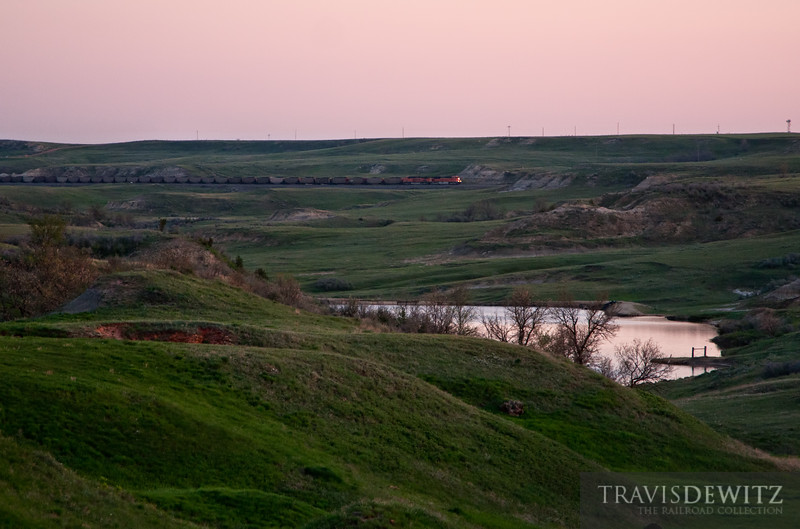 """The sun has just started to peek over the Earth's crust while a loaded BNSF coal train works through the North Dakota Badlands working east towards Belfield.  Travis Dewitz <a href=""""http://www.therailroadcollection.com/latest-works/"""" target=""""_blank"""">The Railroad Collection</a>"""