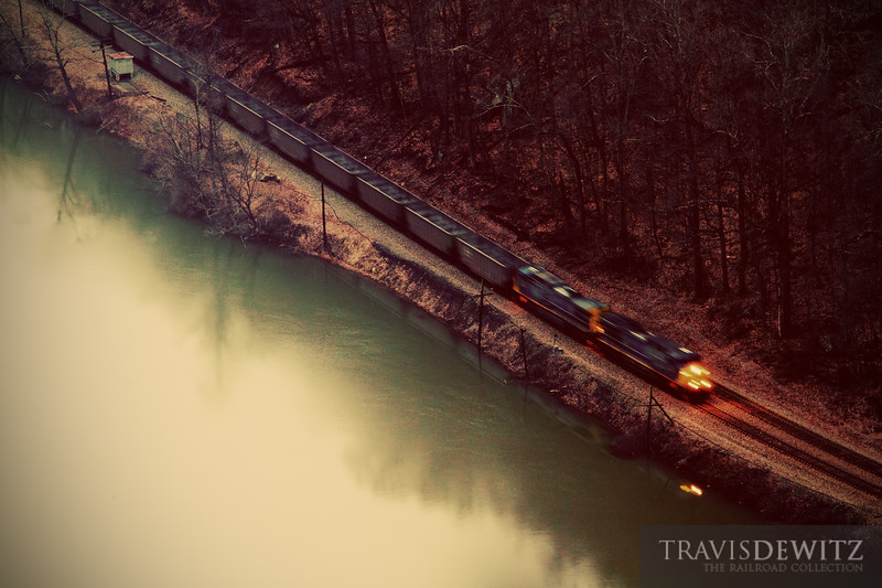 """A quiet dreary early morning at Hawks Nest State Park comes to life as an empty CSX coal train skirts along the bank of the New River.  Travis Dewitz <a href=""""http://www.therailroadcollection.com/latest-works/"""" target=""""_blank"""">The Railroad Collection</a>"""