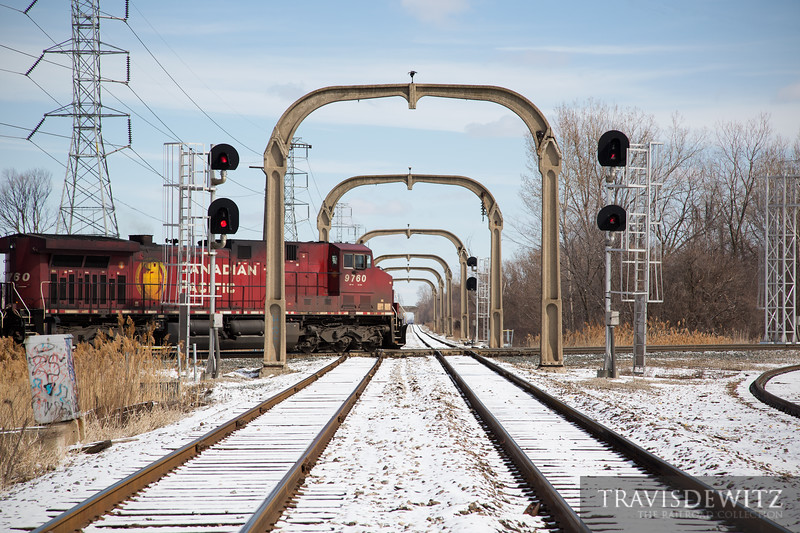 A Canadian Pacific freight train crosses the diamond over Henry Ford's electrified railroad from his Rouge plant south to Flat Rock, then west through Carleton and Maybee, Michigan, a distance of 40 miles. To support the wires, the DT & I erected hundreds of concrete catenary arches.