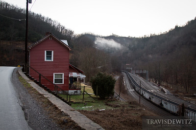 A red house overlooks the coal car holding tracks in Capels, West Virginia.