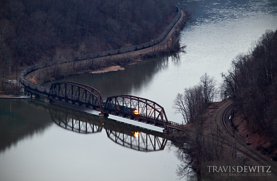 A quiet dreary early morning at Hawks Nest State Park comes to life as an empty CSX coal train skirts along both banks of the New River.