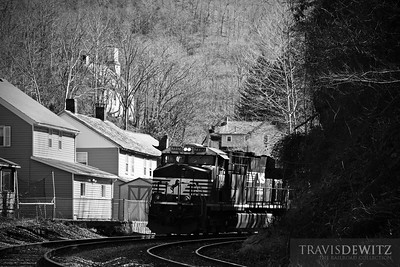 Norfolk Southern 7717 pulls a string of coal cars through the town of Gary, West Virginia on their way towards Welch. The local church can be seen on the hillside towering over the town below.