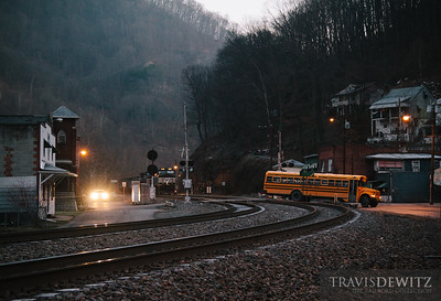 A school bus loads children at the stop near the church as an empty coal train works its way back into the McDowell County coal fields. The train catches a red signal and comes to a stop just before the crossing in Keystone, WV. They will only remain stopped for a couple of minutes which was plenty of time for the bus to cross the tracks and continue their school bus route through town. The next stop is just out of frame between the tracks and highway 52. The sun has yet to reach into the valley as the homes above the town sit in shadow.