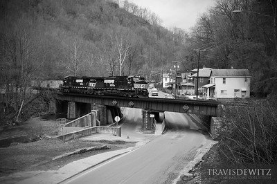 Loaded hoppers full of coal are behing Norfolk Southern power as they curve through the city of Welch, West Virginia heading east towards Bluefield.