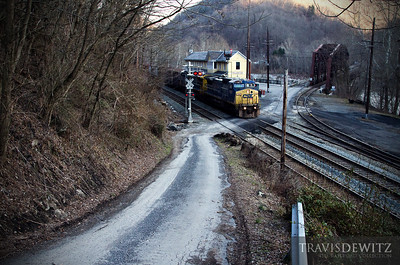 A CSX manifest snakes along the New River and through the old historic town of Thurmond, West Virginia. The tracks that cross the river are operated by the RJ Corman Railroad.