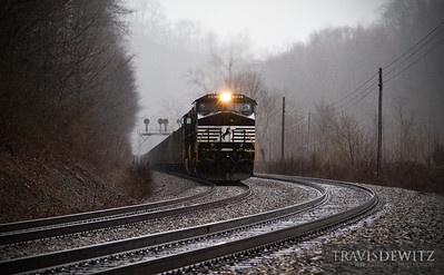 Norfolk Southern 9127 pulls the grade at Landgraff, West Virginia during a thunderstorm downpour. The old N&W CPL signals can be seen in the background.