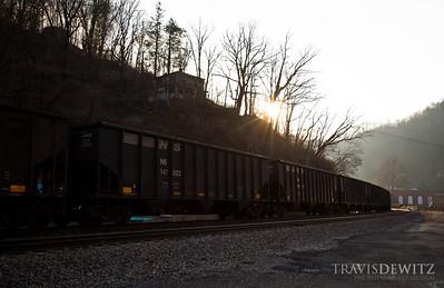 The morning sun breaks over the mountain tops as coal cars rush through Northfork, West Virginia.