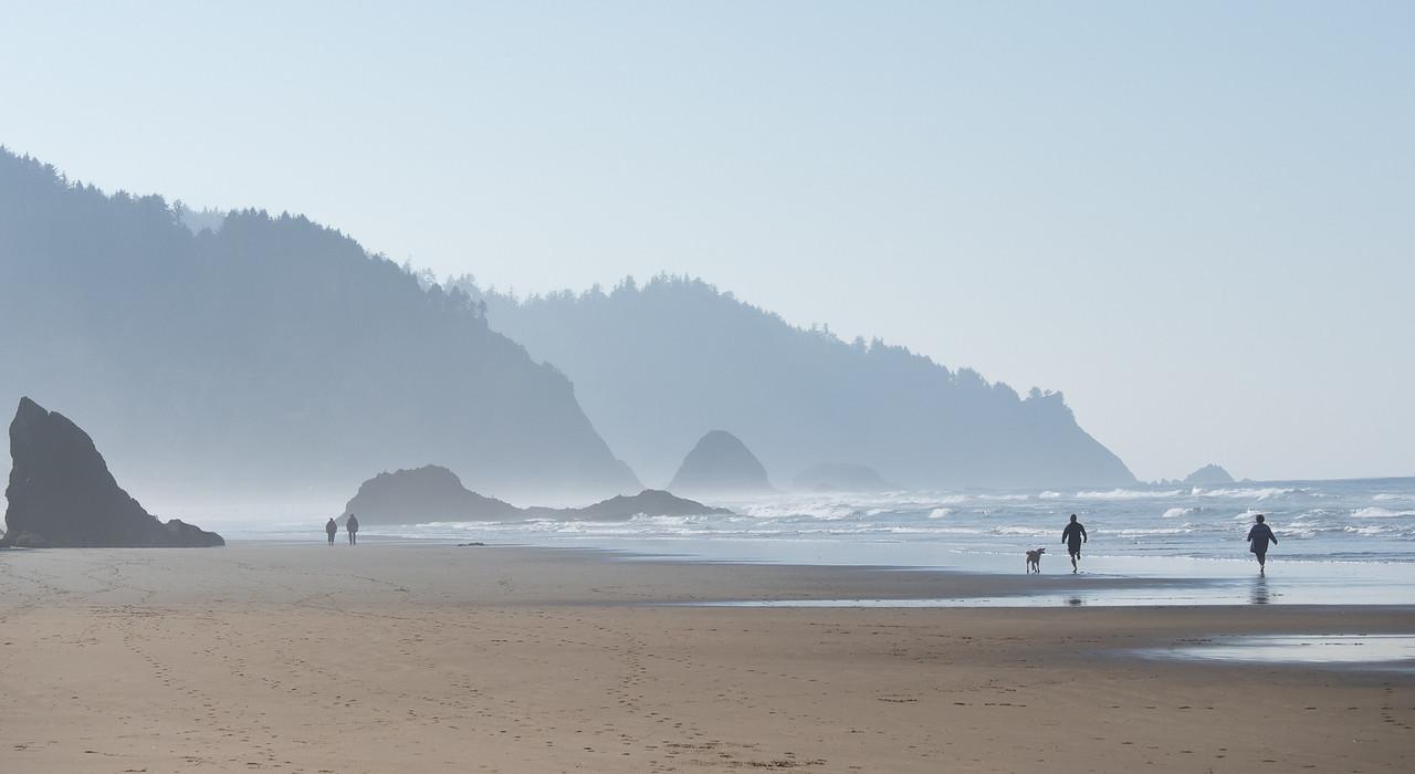 People Walking on Beach in Mist at Hug Point, Oregon