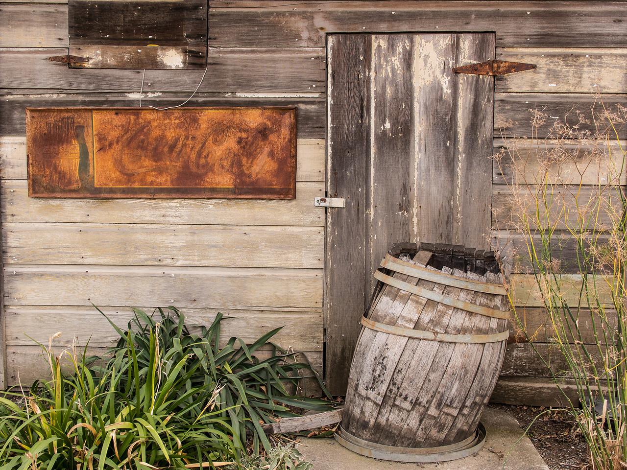 Old Door, Rusted Coca-Cola Sign and Delapidated Wooden Barrel