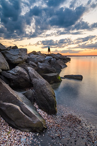 Girl watching sunset on a jetty (vertical)
