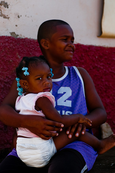 a young Boy holds his little sister who's not really sure what to think about a white man walking through her village.  This was in the town of Punta Gorda.