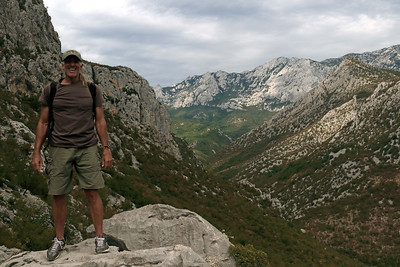 Paklencia National Park - along the trail to Manita Pec Cave - viewing NW up the Velika (Grand) Paklenica Valley, a karst river canyon, meandering about 9 mi, (14 km) along the southern slopes of the Velebit Mountain -  here beyond the slope of Vidakov (L), to Orlov Peak (R), then between distal to Vaganski Peak (above the sunlight patch), rising about 5,764 ft. (1,757 m) - Zadar county - N Dalmatia region - Croatia - NW Balkan Peninsula - Eastern Europe.