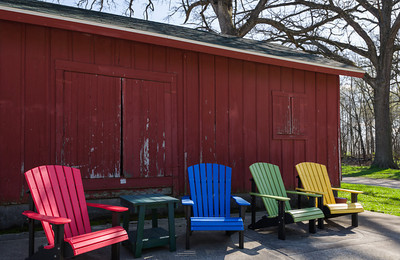 Colorful Adirondack Chairs in Front of Old Red Wooden Building
