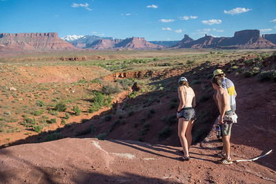 "Marcella Fisher, Zane Lyon, and Zack Shepard look over the edge of a geologic ""nick point"" on the north side of the Colorado River.  The La Sal mountains rise in the distance with the majestic buttes of Castle Valley filling the foreground."