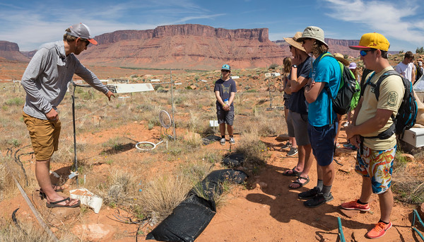 Armin, a USGS field technician, educates the students about the technical challenges of studying plants and crypto-biotic soils in a 10-year Department of Energy study on climate change.