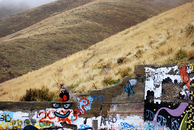 I don't know if you intended to capture the large eyes and smiling mouth below the person, but it works well.  I also like the composition of rolling ridges behind the relatively narrow splash of graffiti color.  It places the graffiti pit in context of the open slopes of Carbonate mtn.  Nice work.