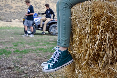 Nice shot, good use keeping the depth of field narrow.  I think it would be stronger is the entire ATV was shifted to the left (this can be accomplished with a little shift in the photogs position) and the legs to the right.  As it is there is too much hay bale in the photo, kind of distracting.  I really like how the girls legs are cropped.  It implies a story about girls versus boys that is up to the viewers imagination.