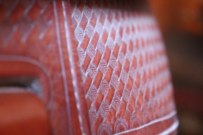 I like this also and think your plane of focus pulls the eye to the most interesting point.  I would crop out more of the left side of the image bringing the cross-hatched leather work into the left third.  Overall focus is soft which might be due to a slow shutter speed, especially if this was taken in your tack shed.  That is always a challenge.  You can brace your shoulder against things, and hold you breath when pressing the shutter button to help with this.