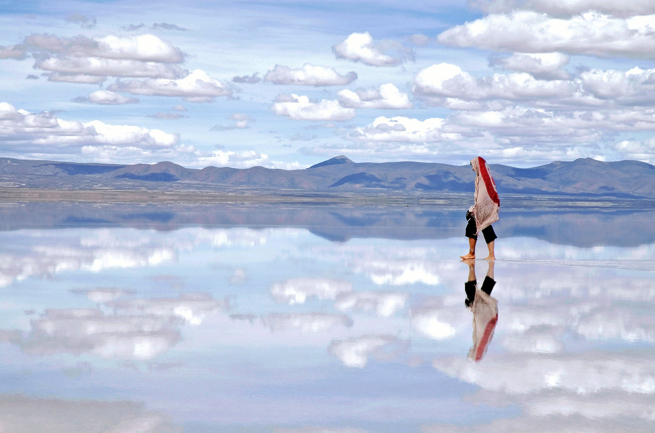 Uyuni, Bolivia: The Bolivian salt flats. The Bolivian salt flats are a 12,000 square km of bright white expanse. In the summer though it rains enough that they are covered in water, sometimes more than a meter. It makes for an incredible reflection.  At one of the many stops on our 4x4 tour across the Salt Flats I managed to escape from the horde of tourists and capture this photo. I have no idea who this woman is or where she came from. She seemingly appeared from nowhere only allowing me the opportunity for just one shot; I lined it up and took the perfect photo of her just before she disappeared behind the crowd. This is one of my favorite photos, it gives you a glimpse of the incredible beauty of the place.  This photo will be appearing at the Smithsonian Institute in Washington DC from July 2009 - January 2010